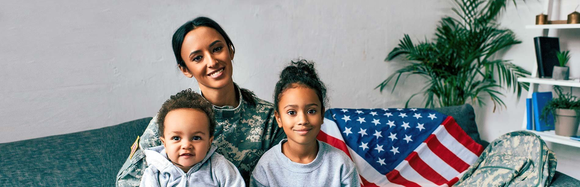 Military mom with young son and daughter sitting in home